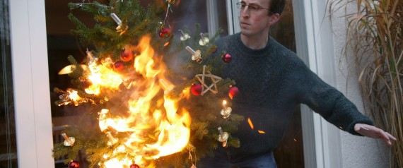 Man is running with a burning christmas tree out of the house.